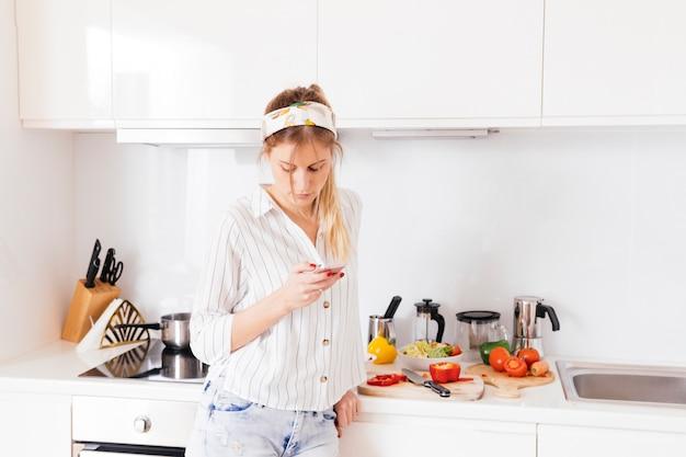 Femme debout près du plan de travail de la cuisine à l'aide d'un téléphone portable Photo gratuit