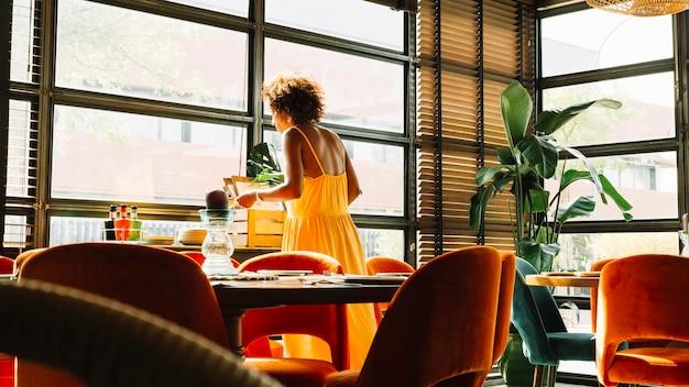 Femme debout près de la fenêtre du restaurant Photo gratuit