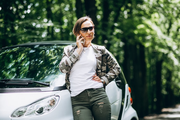 Femme debout près de la voiture dans le parc à l'aide de téléphone Photo gratuit
