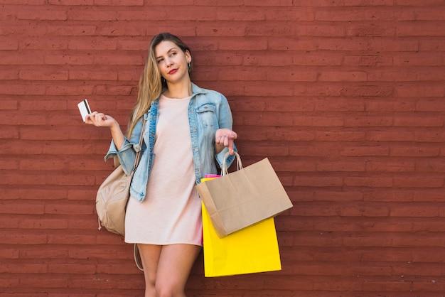 Femme debout avec des sacs à provisions et carte de crédit au mur de briques Photo gratuit