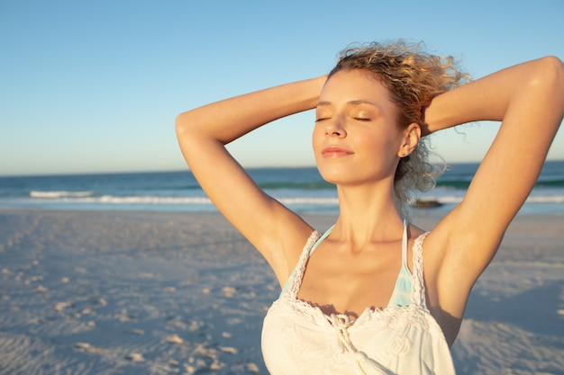 Femme debout avec les yeux fermés sur la plage Photo gratuit