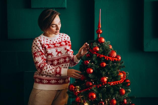 Femme décorer un arbre de noël avec des jouets rouges Photo gratuit