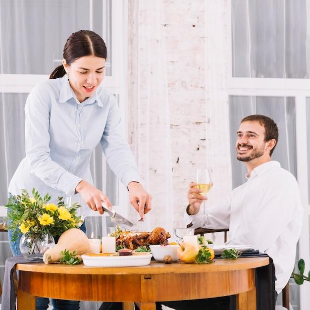 Femme découpant du poulet cuit au four à la table de fête Photo gratuit