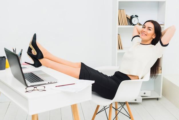 Femme, délassant, mettre jambes, sur, table, dans, bureau Photo gratuit