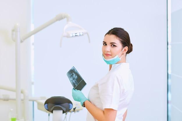 Une femme dentiste avec lieu de travail de rayons x en cabinet dentaire Photo Premium