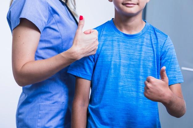 Femme dentiste avec patient gesticulant pouce en l'air Photo gratuit