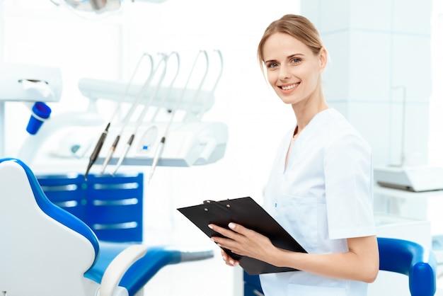 Une femme dentiste tient une tablette pour ses papiers. Photo Premium
