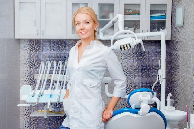 Une femme dentiste en uniforme blanc pose contre un appareil dentaire dans un cabinet dentaire Photo Premium