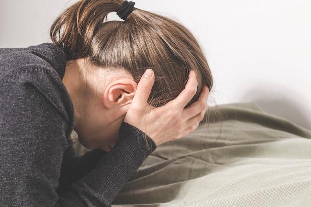 Une femme dépressive pleure, les mains couvrant son visage, allongée sur le canapé. Photo Premium