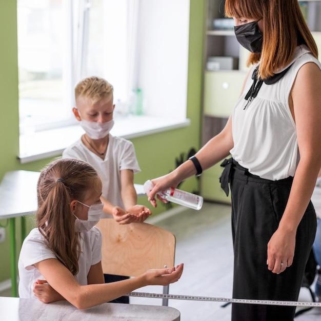 Femme Désinfectant Les Mains De Ses élèves Photo Premium