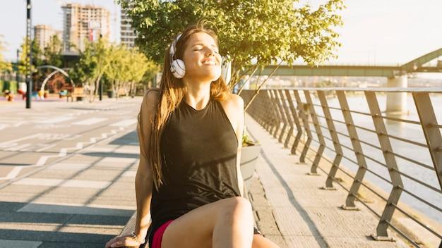 Femme détendue, écoutant de la musique sur le casque à l'extérieur Photo gratuit