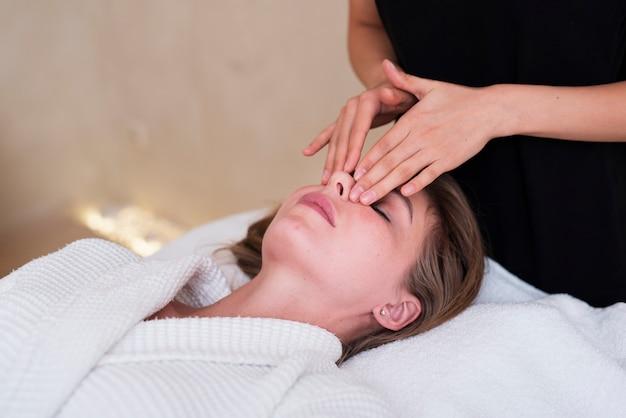 Femme Détendue Faisant Un Massage Du Visage Photo gratuit
