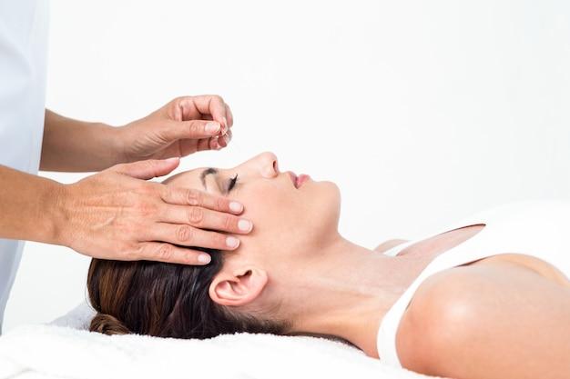 Femme détendue recevant un traitement d'acupuncture Photo Premium