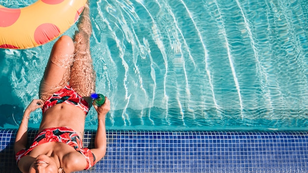 Femme de détente à côté de la piscine Photo gratuit