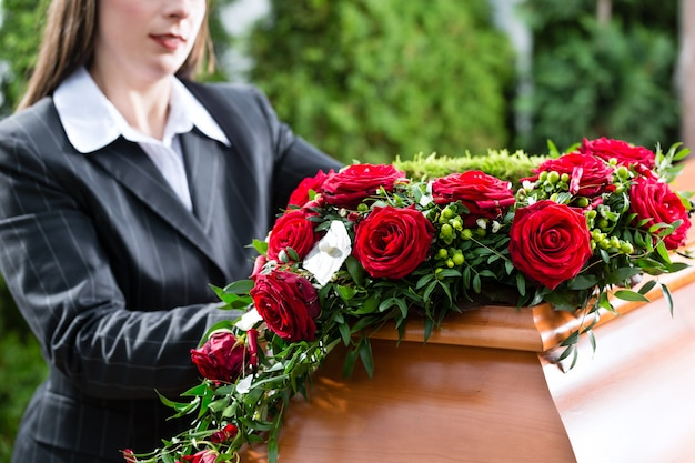 Femme en deuil aux funérailles avec cercueil Photo Premium