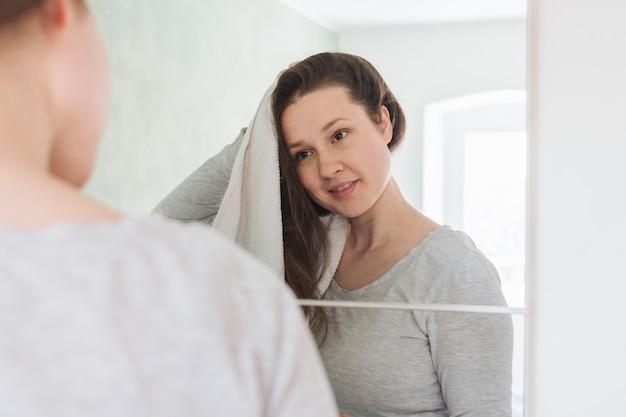 Femme Devant Miroir Dans Salle De Bain Photo gratuit