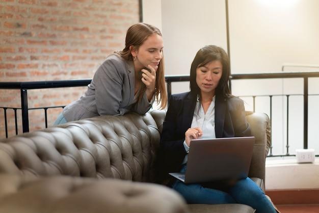 Femme discutant avec désinvolture des idées sur un canapé dans le lieu de travail moderne Photo Premium