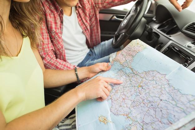 Femme, doigt pointé, sur, emplacement, carte navigation, à, homme, dans voiture Photo gratuit
