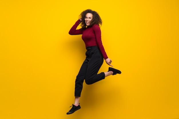 Femme dominicaine aux cheveux bouclés sautant par-dessus un mur jaune isolé Photo Premium