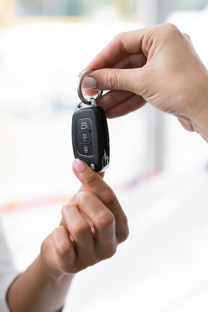 Femme donnant la clé de la voiture Photo gratuit
