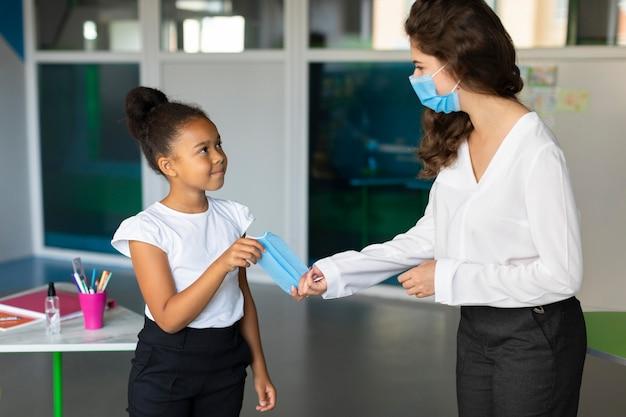Femme Donnant Un Masque Médical à Un étudiant Photo gratuit
