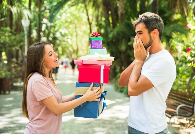 Femme donnant une pile de cadeaux à son petit ami surpris Photo gratuit