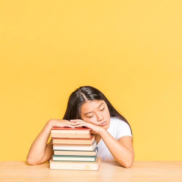 Femme dormant sur une pile de livres Photo gratuit