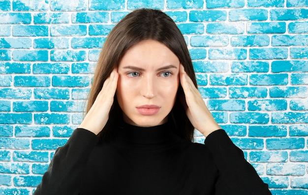 Une Femme Avec Une Douleur Dans La Tête Tient à Sa Tête Une Migraine Photo Premium