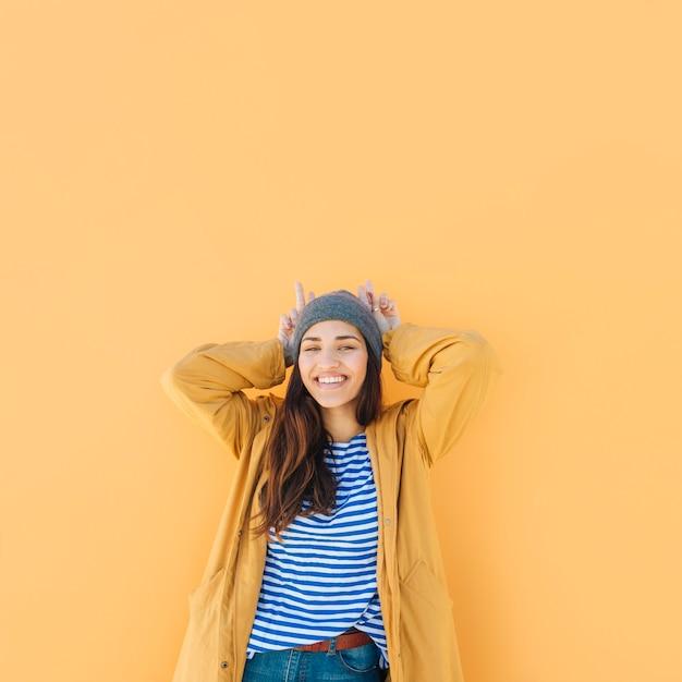 Femme drôle faisant corne avec les mains en regardant la caméra sur fond uni Photo gratuit