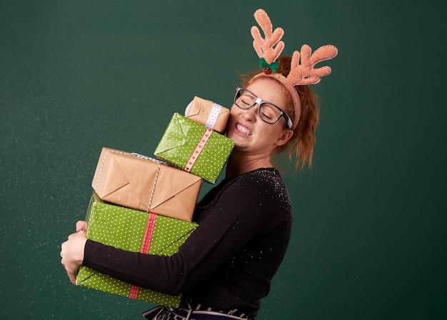 Femme Drôle Portant Pile De Cadeaux De Noël Lourds Photo gratuit