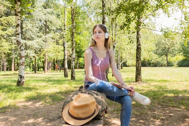 Femme écoutant de la musique dans la forêt Photo gratuit