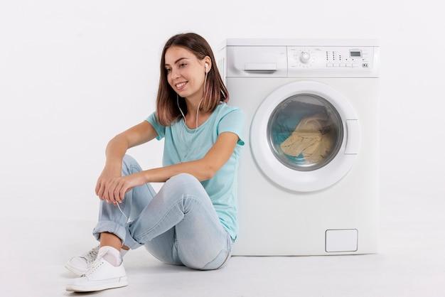 Femme écoutant de la musique et faisant la lessive Photo gratuit