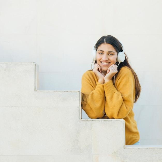 Femme écoutant de la musique en regardant la caméra Photo gratuit