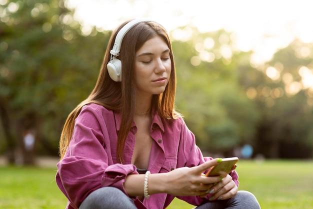 Femme écoutant De La Musique Et Regardant Son Téléphone Photo Premium