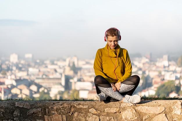 Femme écoutant de la musique vue de face Photo gratuit