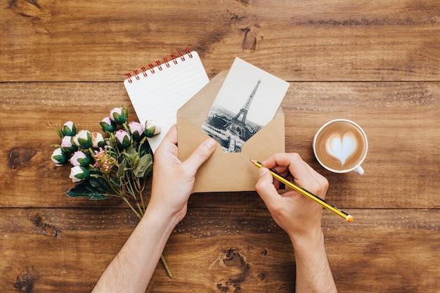 Femme écrivant une adresse dans une enveloppe Photo gratuit