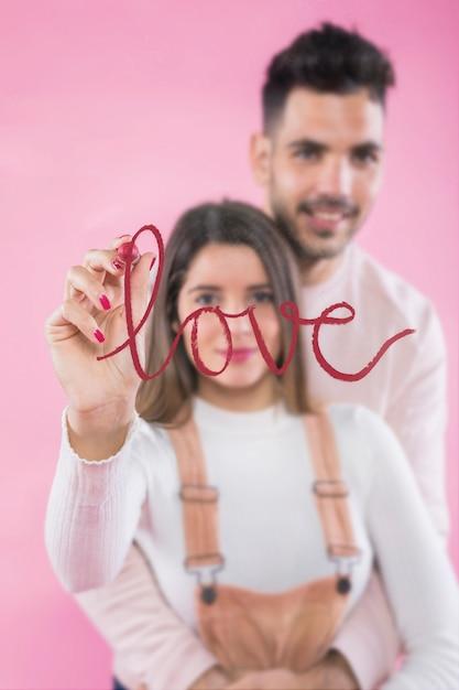 Femme écrivant l'amour sur le verre avec le rouge à lèvres Photo gratuit