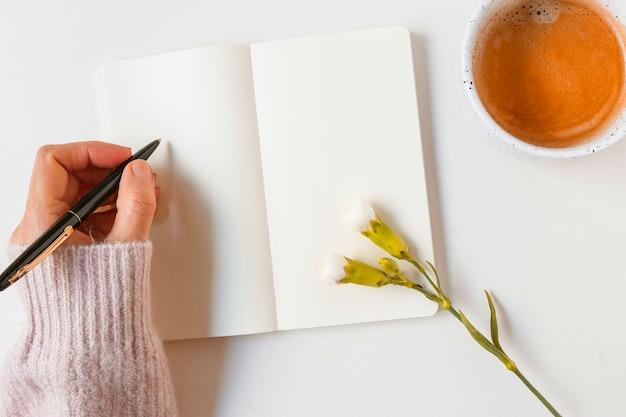 Femme écrivant sur un cahier vierge avec un stylo sur fond blanc Photo gratuit