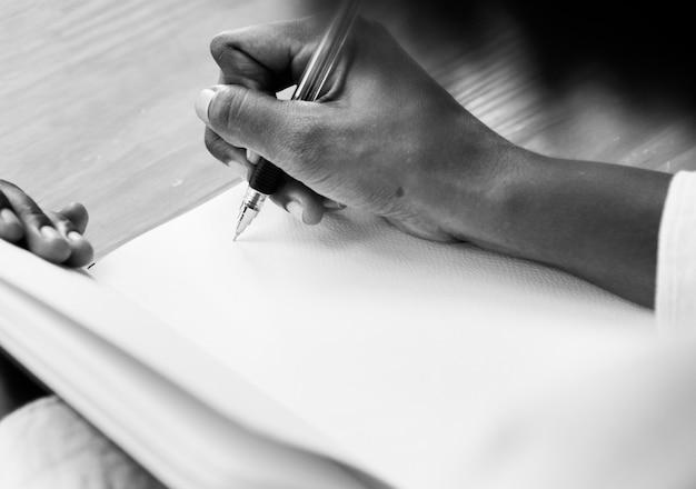 Femme écrivant dans un cahier Photo gratuit