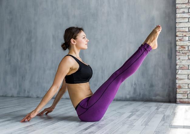 Femme effectuant une pose de bateau de yoga Photo gratuit