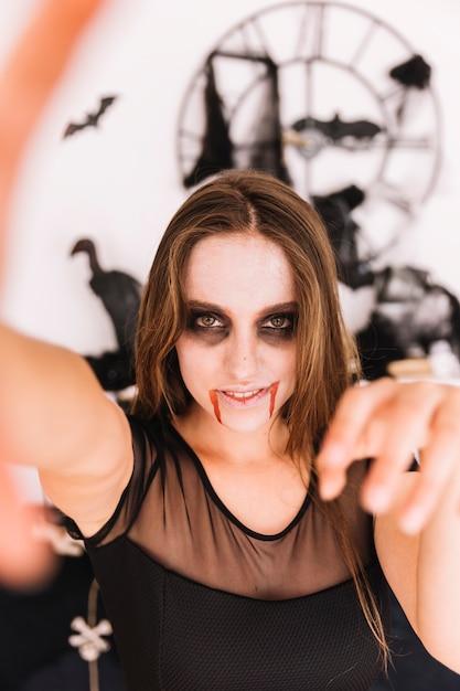 Femme, à, effrayant, halloween, sinistre, devant, mur, à, chauves-souris Photo gratuit