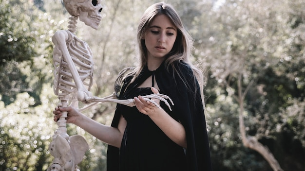 Femme Effrayée Dans Des Vêtements De Sorcier Tenant Un Squelette Photo gratuit