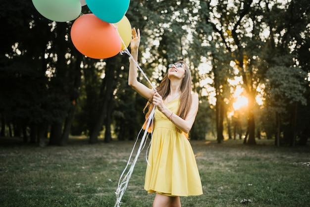 Femme élégante au soleil regardant des ballons Photo gratuit