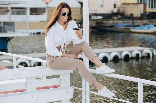 Une femme élégante, buvant un café et marchant le long du front de mer dans une chaude journée d'été au coucher du soleil Photo Premium
