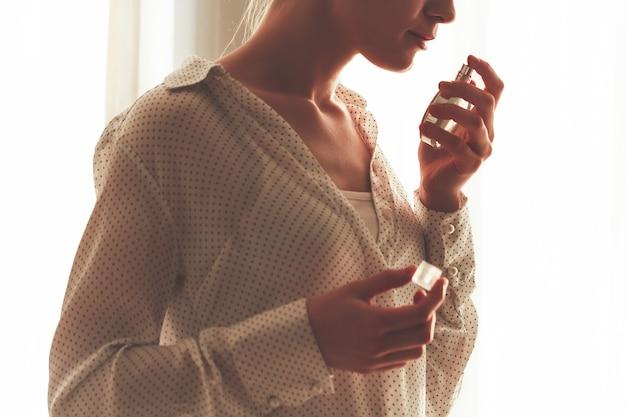 Femme élégante en chemisier avec une bouteille de parfum préféré. Photo Premium