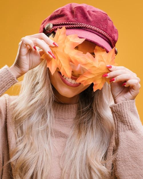 Femme élégante couvrant ses yeux avec les feuilles d'automne Photo gratuit