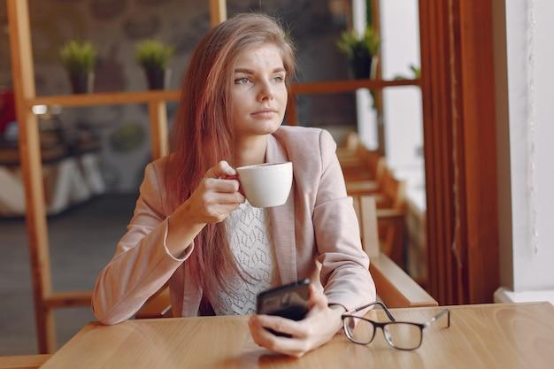 Femme élégante Dans Une Veste Rose, Passer Du Temps Dans Un Café Photo gratuit