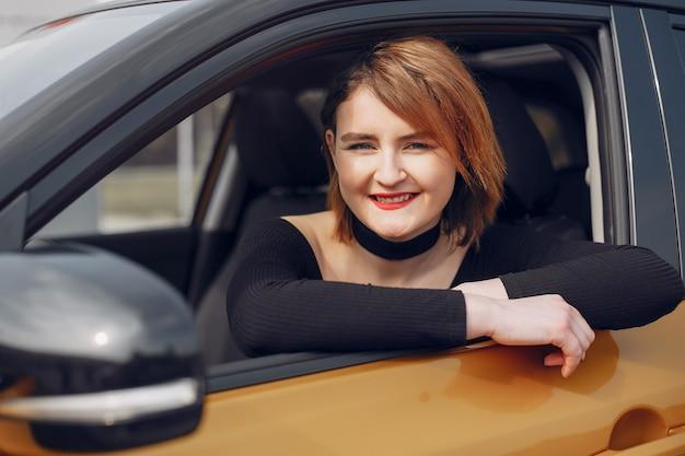 Femme élégante et élégante dans un salon de l'automobile Photo gratuit