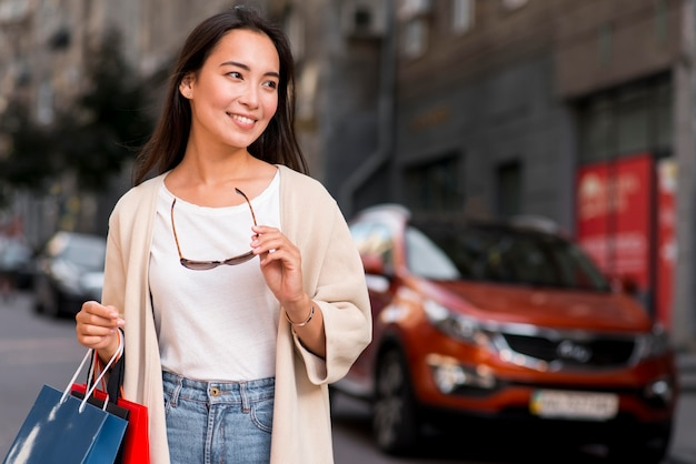 Femme élégante Avec Des Lunettes De Soleil Posant à L'extérieur Avec Des Sacs à Provisions Photo gratuit