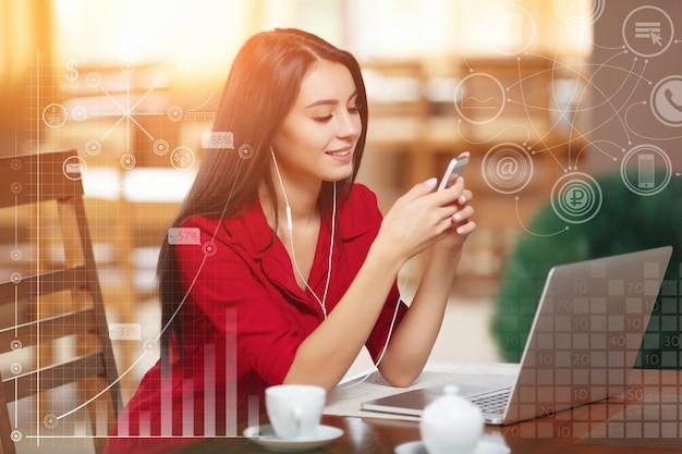 Femme élégante avec un ordinateur portable écoutant de la musique Photo gratuit